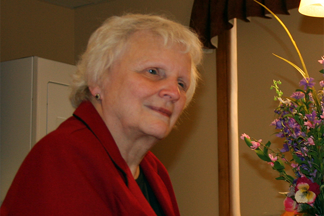 Vision Forward Board Member and volunteer Nona Graves in a red jacket, with a bouquet of spring flowers nearby.