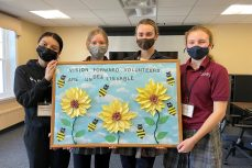 Photo of four students holding a bulletin board